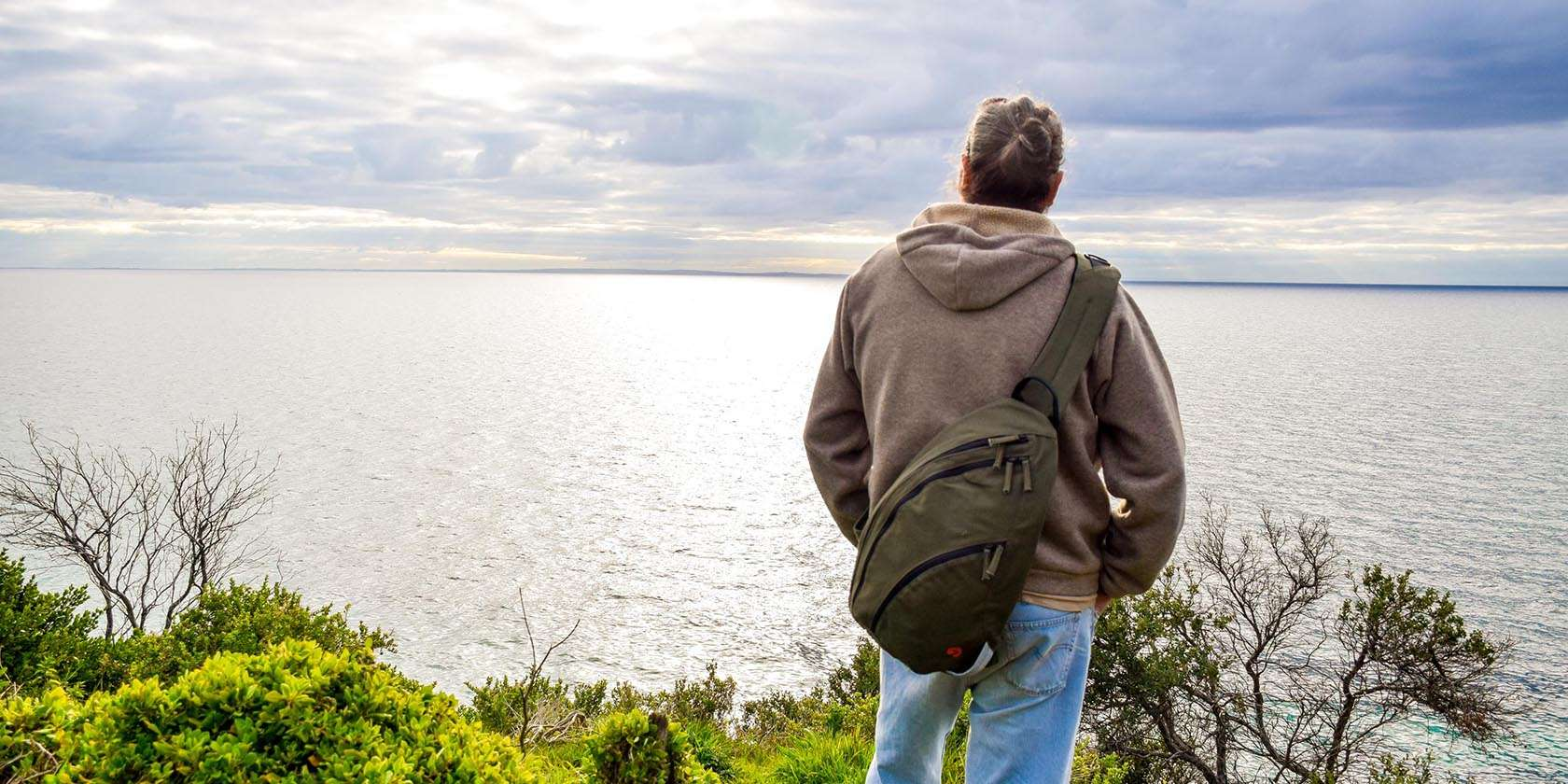 Male Model wearing olive green sling backpack at the beach