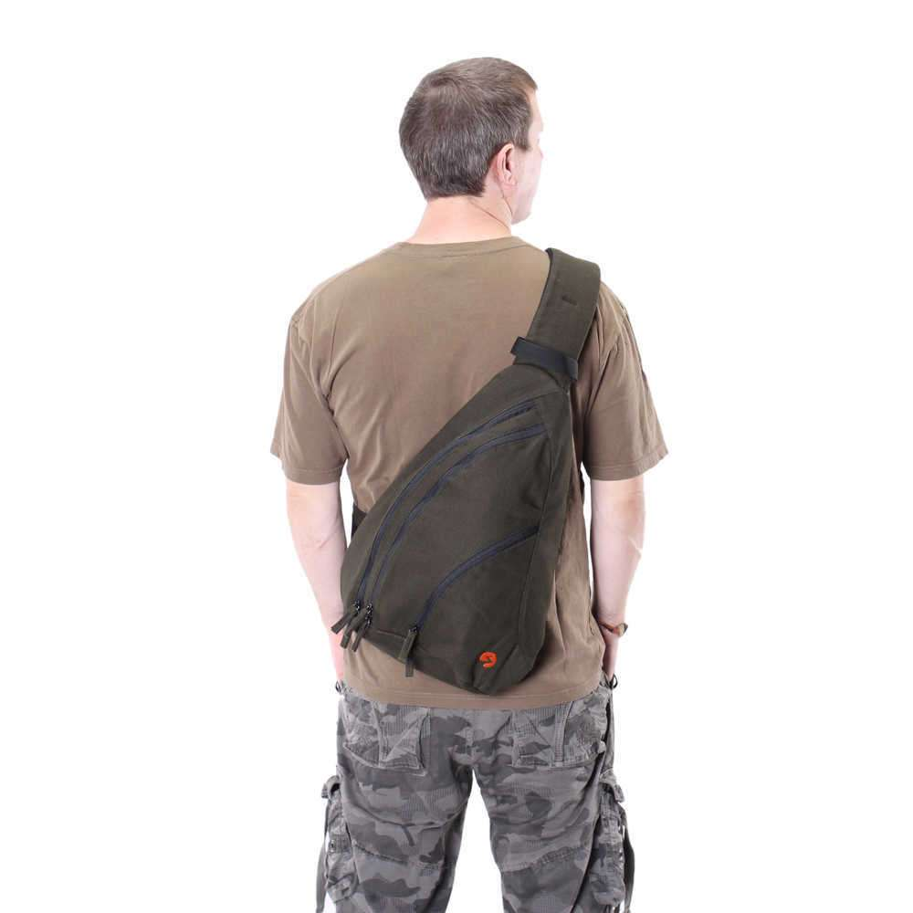 Male model wearing a large green canvas sling pack.